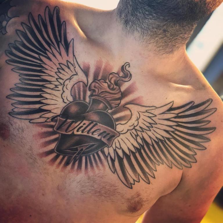 Тату сердце с крыльями на груди