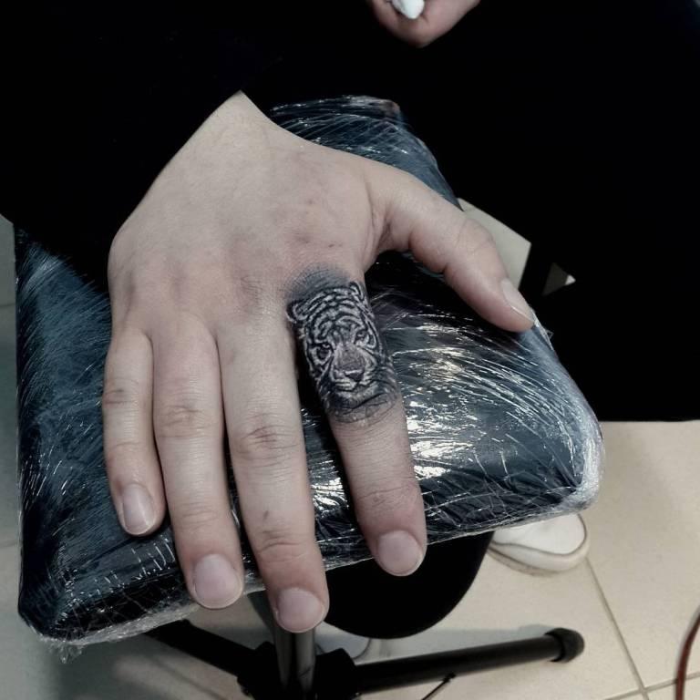 Маленькое тату на пальце у мужчины